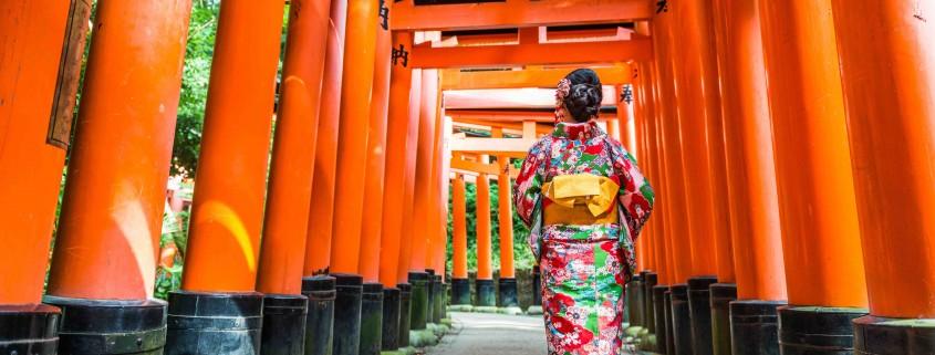 Women in kimono stand at Red Torii gates in Fushimi Inari shrine